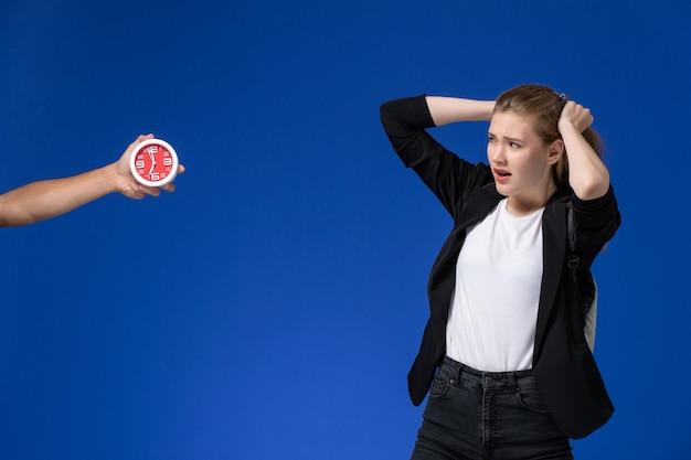 Vooraanzicht vrouwelijke student in zwart jasje rugzak dragen op lichtblauwe muur school college universiteit lessen tijd