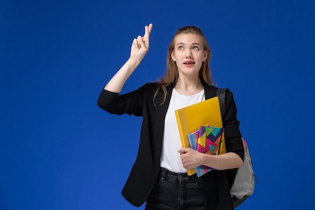 Vooraanzicht vrouwelijke student in zwarte jas draagt rugzak met bestanden met voorbeeldenboeken die haar vingers kruisen op blauwe muur college universitaire les