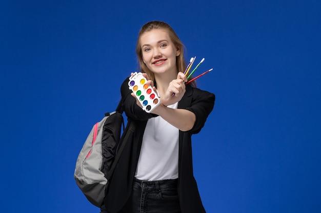 Vooraanzicht vrouwelijke student in zwarte jas dragen rugzak met verf voor tekenen en kwast op blauwe muur tekenen kunstacademie college lessen