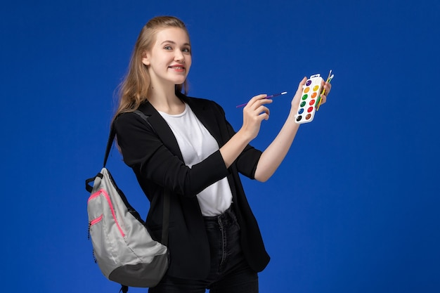 Vooraanzicht vrouwelijke student in zwarte jas dragen rugzak met verf voor tekenen en kwast op lichtblauwe muur tekenen kunstacademie