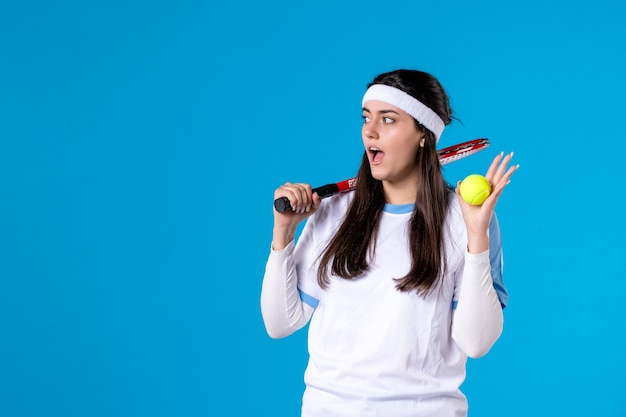 Vooraanzicht vrouwelijke tennisspeelster met tennisracket en bal