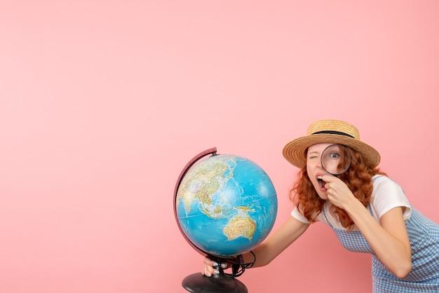 Vooraanzicht vrouwelijke toerist die bol met meer magnifier onderzoekt