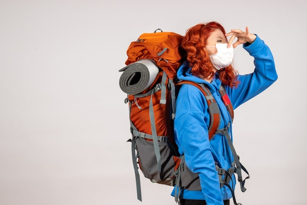 Vooraanzicht vrouwelijke toerist die in bergreis gaat met rugzak die haar neus sluit