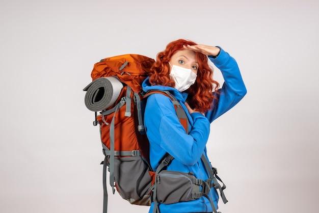 Vooraanzicht vrouwelijke toerist die in bergreis in masker met rugzak gaat