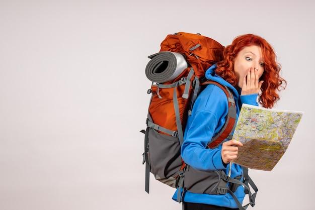 Vooraanzicht vrouwelijke toerist die in bergreis met rugzak en kaart gaat Gratis Foto
