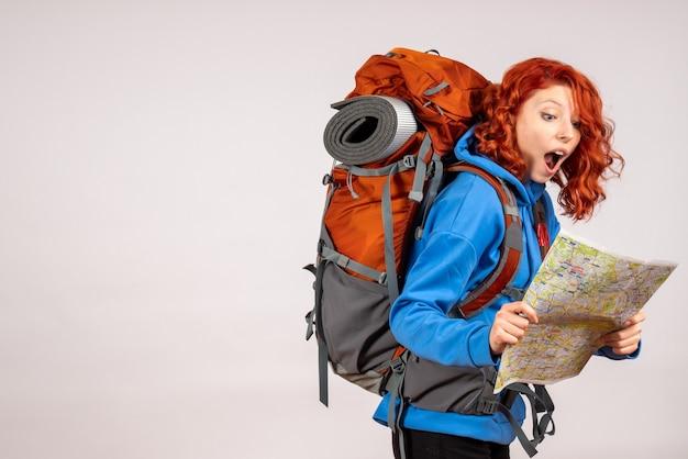 Vooraanzicht vrouwelijke toerist die in bergreis met rugzak en kaart gaat
