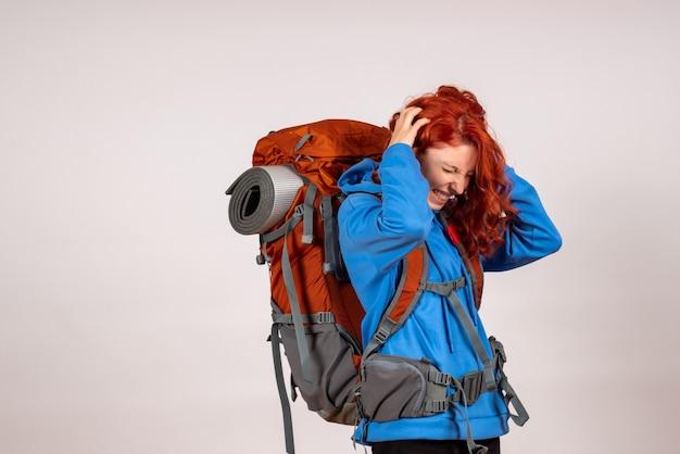 Vooraanzicht vrouwelijke toerist die in bergreis met rugzak gaat die hoofdpijn heeft