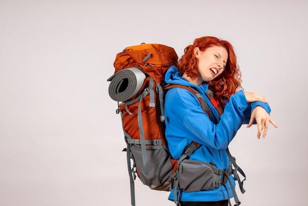 Vooraanzicht vrouwelijke toerist gaat in bergreis met rugzak met pijn in haar arm