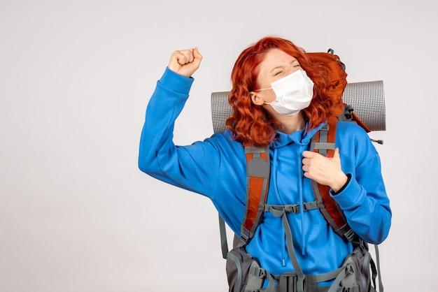 Vooraanzicht vrouwelijke toerist in masker met haar rugzak verheugend