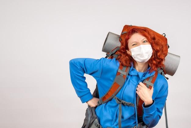 Vooraanzicht vrouwelijke toerist in masker met haar rugzak