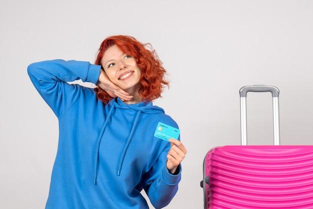Vooraanzicht vrouwelijke toerist met bankkaart en lachend