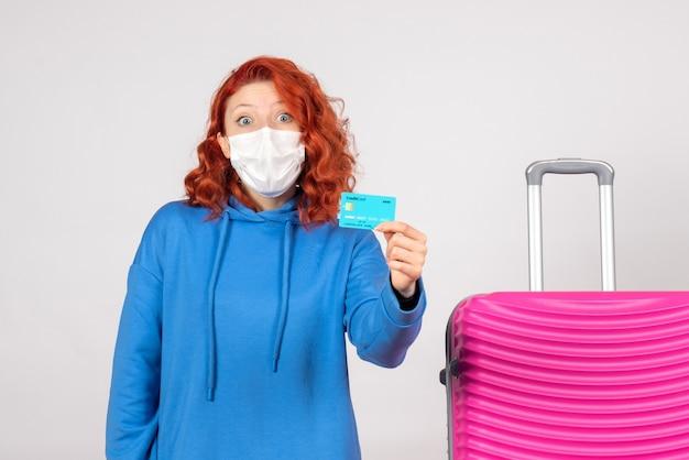 Vooraanzicht vrouwelijke toerist met bankkaart in masker