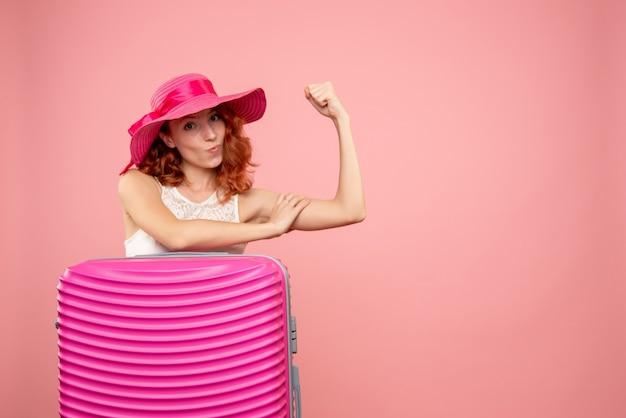 Vooraanzicht vrouwelijke toerist met roze zak buigen