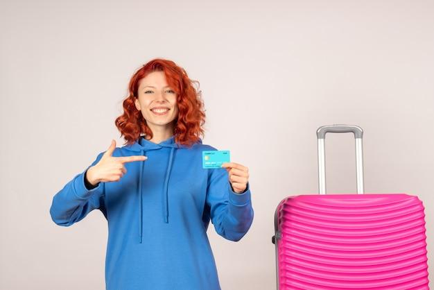 Vooraanzicht vrouwelijke toerist met roze zak en bankkaart te houden