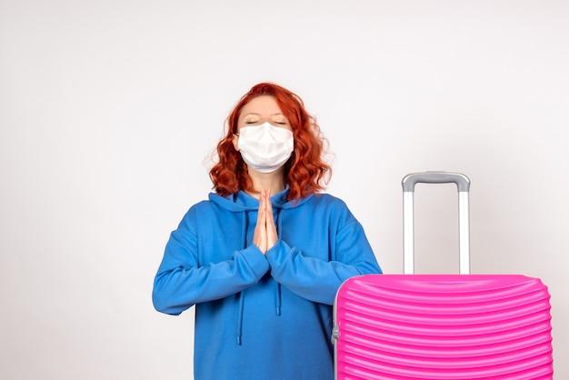 Vooraanzicht vrouwelijke toerist met roze zak in masker