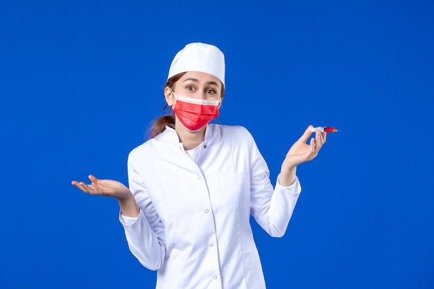 Vooraanzicht vrouwelijke verpleegster in wit medisch pak met rood masker en injectie in haar handen op blauw