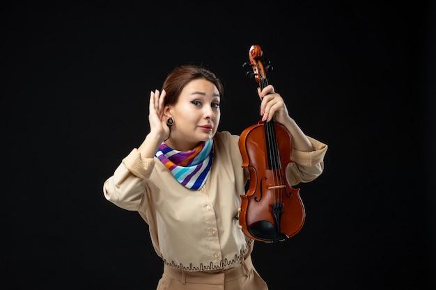 Vooraanzicht vrouwelijke violist die haar viool houdt die op donkere muur luistert
