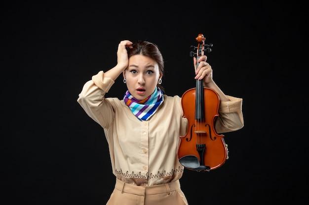Vooraanzicht vrouwelijke violist die haar viool op een donkere muur houdt concert melodie speel instrument emotie vrouw performance muziek