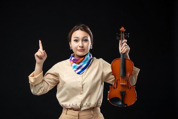 Vooraanzicht vrouwelijke violist die haar viool op een donkere muur houdt concert melodie speel instrument vrouw prestatie emotie
