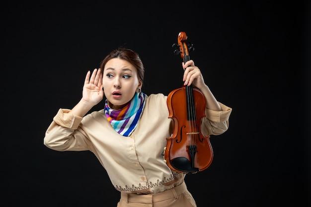 Vooraanzicht vrouwelijke violist die haar viool op een donkere muur houdt muziek concert melodie instrument vrouw prestatie emotie speelt