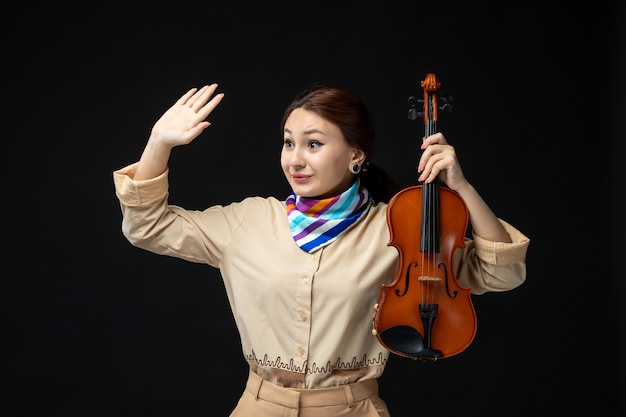 Vooraanzicht vrouwelijke violiste die haar viool houdt die op donkere muur zwaait concert melodie instrument vrouw prestatie muziek emotie spel