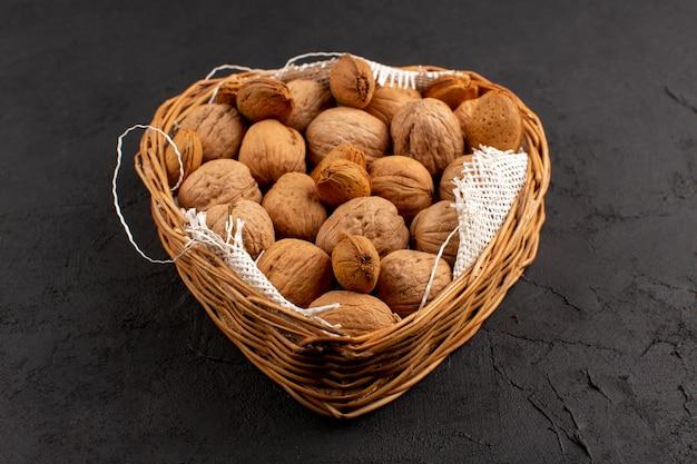 Vooraanzicht walnoten in bruine mand op het donker
