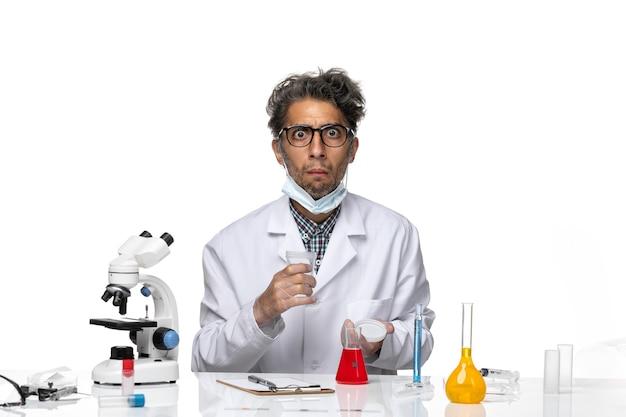 Vooraanzicht wetenschapper op middelbare leeftijd die in wit medisch kostuum lege kolf houdt