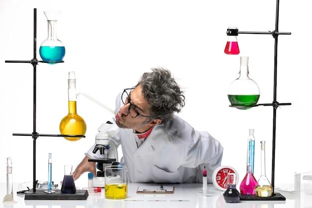 Vooraanzicht wetenschapper van middelbare leeftijd in medisch pak met behulp van microscoop