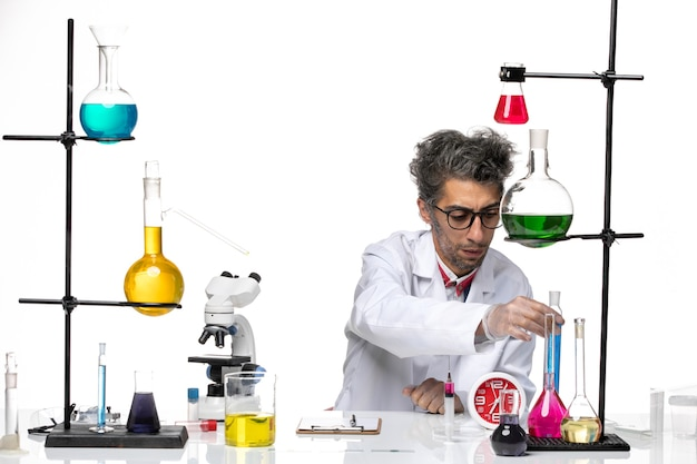 Vooraanzicht wetenschapper van middelbare leeftijd in medisch pak met blauwe oplossing