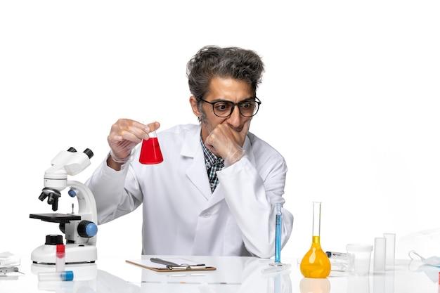 Vooraanzicht wetenschapper van middelbare leeftijd in medisch pak met rode oplossing