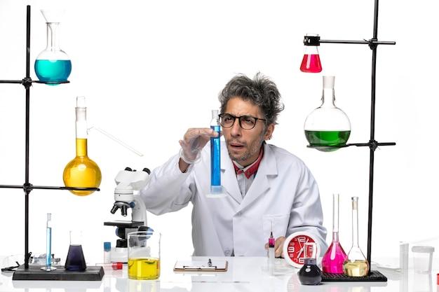 Vooraanzicht wetenschapper van middelbare leeftijd in medisch pak werken met blauwe oplossing