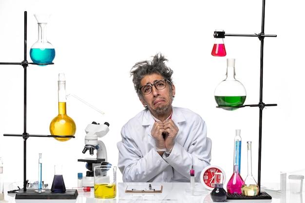 Vooraanzicht wetenschapper van middelbare leeftijd in medische pak zitten en bedelen