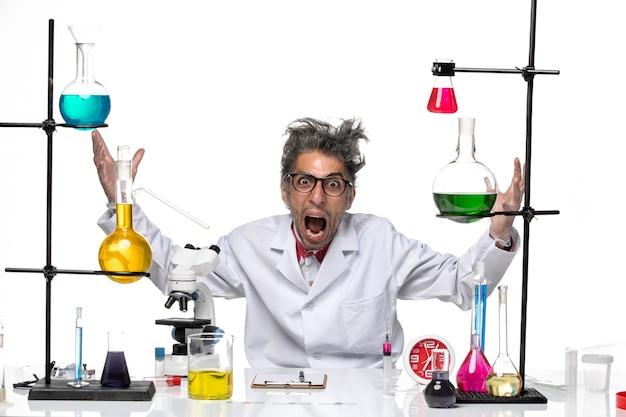 Vooraanzicht wetenschapper van middelbare leeftijd in medische pak zitten en schreeuwen