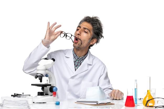Vooraanzicht wetenschapper van middelbare leeftijd in speciaal pak dat zijn zonnebril bevestigt