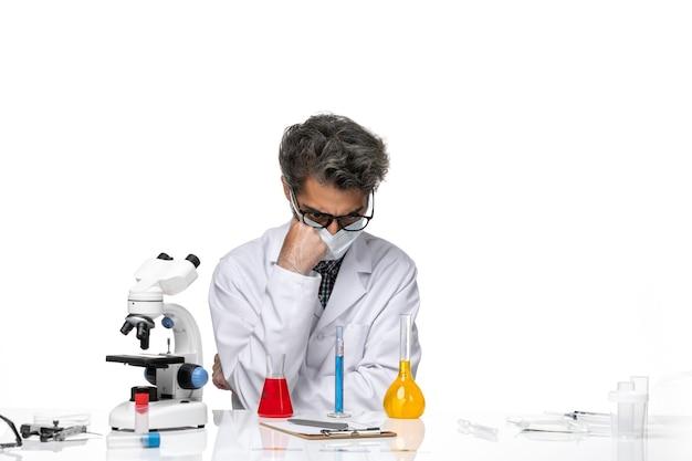 Vooraanzicht wetenschapper van middelbare leeftijd in speciaal pak die met verschillende oplossingen werkt