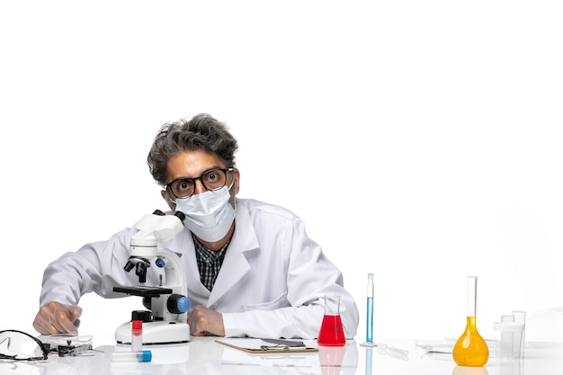 Vooraanzicht wetenschapper van middelbare leeftijd in speciaal wit pak met behulp van microscoop