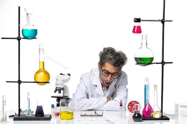 Vooraanzicht wetenschapper van middelbare leeftijd in wit medisch pak moe