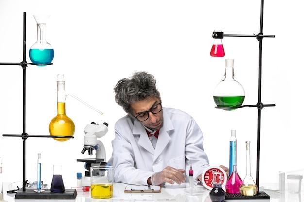 Vooraanzicht wetenschapper van middelbare leeftijd in wit medisch pak werken met oplossingen