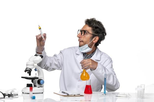 Vooraanzicht wetenschapper van middelbare leeftijd in witte medische pak vullende injectie