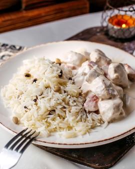 Vooraanzicht wit vlees segmenten samen met rijst en bonen op de bruin houten bureau en lichte vloer