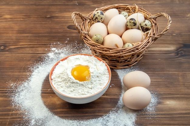 Vooraanzicht witte bloem met eieren in mand op bruine achtergrond voedsel deeg taart bak gebak rauwe keuken cake