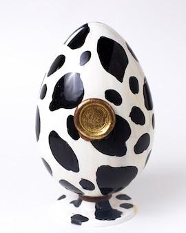 Vooraanzicht witte en zwarte chocolade ei kleur met een gouden zegel op standaard