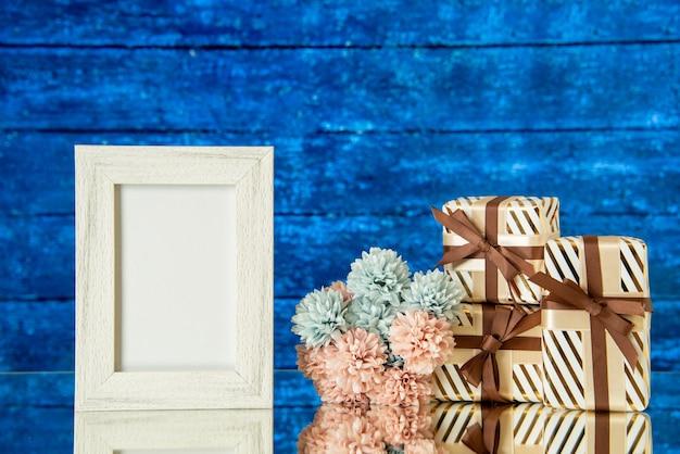 Vooraanzicht witte fotolijst vakantie geschenkdozen bloemen weerspiegeld op spiegel met een blauwe houten achtergrond