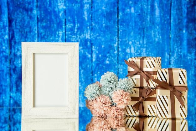 Vooraanzicht witte fotolijst vakantiegeschenken weerspiegeld op spiegel met een blauwe houten achtergrond