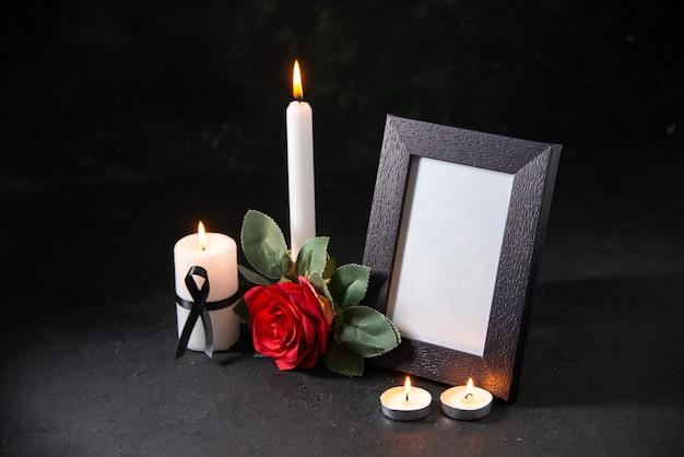 Vooraanzicht witte kaars met fotolijst en bloem op het donkere oppervlak