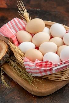 Vooraanzicht witte kippeneieren in mand met handdoek op het donkere oppervlak