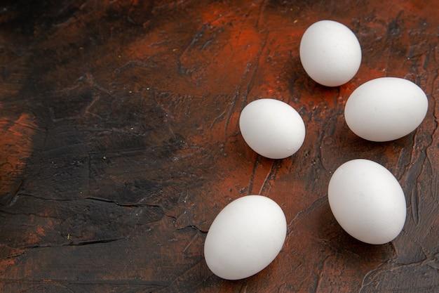 Vooraanzicht witte kippeneieren op het donkere oppervlak