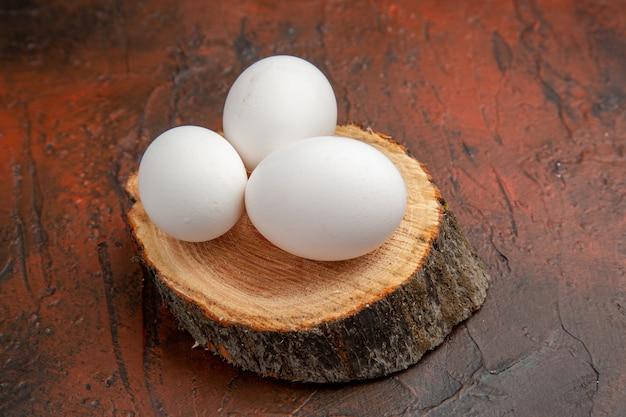 Vooraanzicht witte kippeneieren op hout op donkere ondergrond
