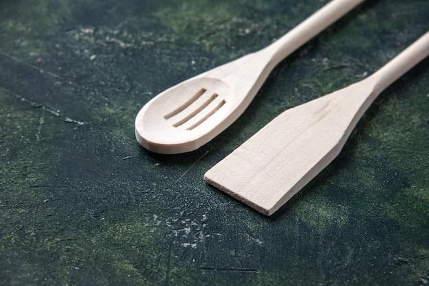 Vooraanzicht witte plastic gebruiksvoorwerpen op donkere achtergrond plastic vork bestek houten mes keuken voedsel foto's