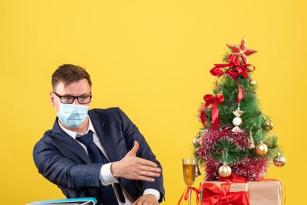 Vooraanzicht zakenman geven hand zittend aan de tafel in de buurt van kerstboom en presenteert op gele achtergrond